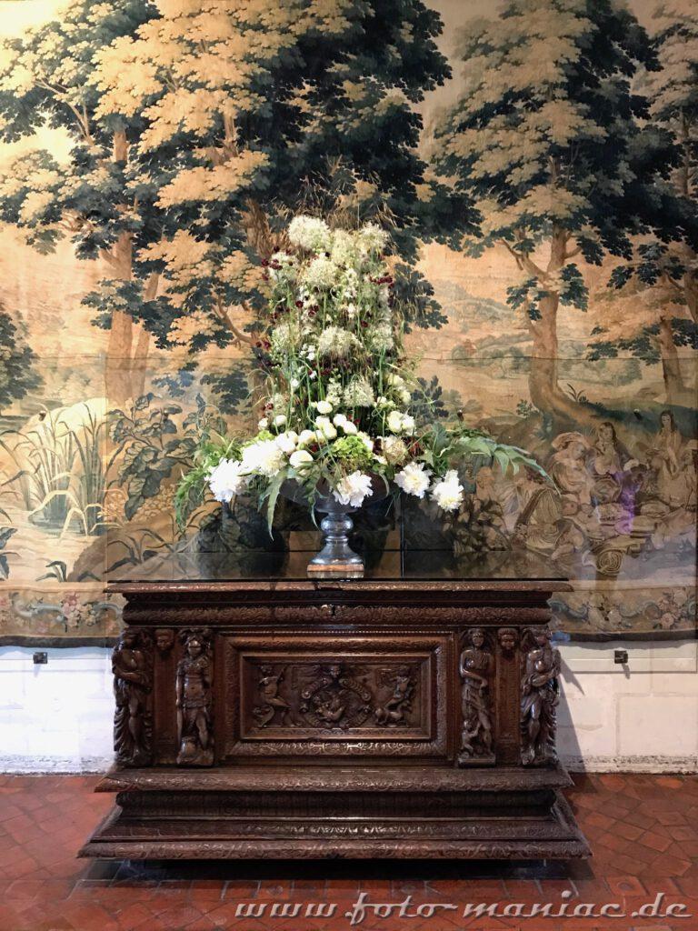 Blumearrangement vor einem kostbaren Wandteppich