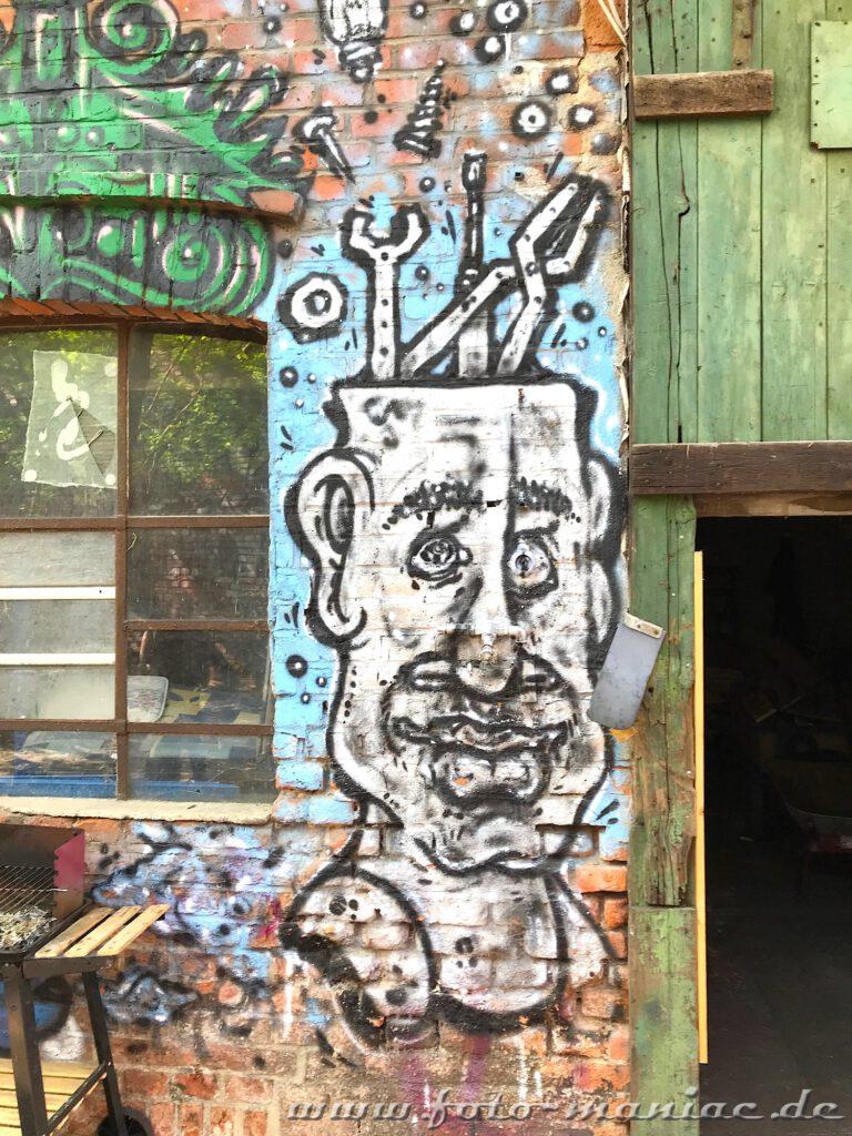 Männerkopf-Graffito an Wand