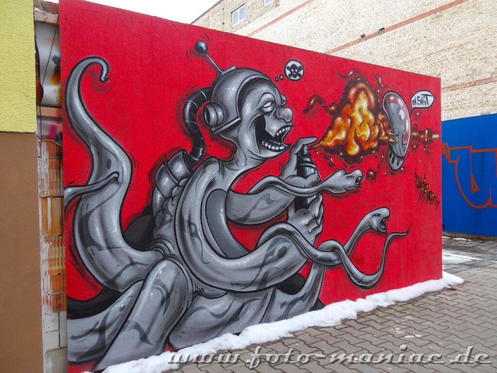 Alien-Graffito bedient Sprayflasche