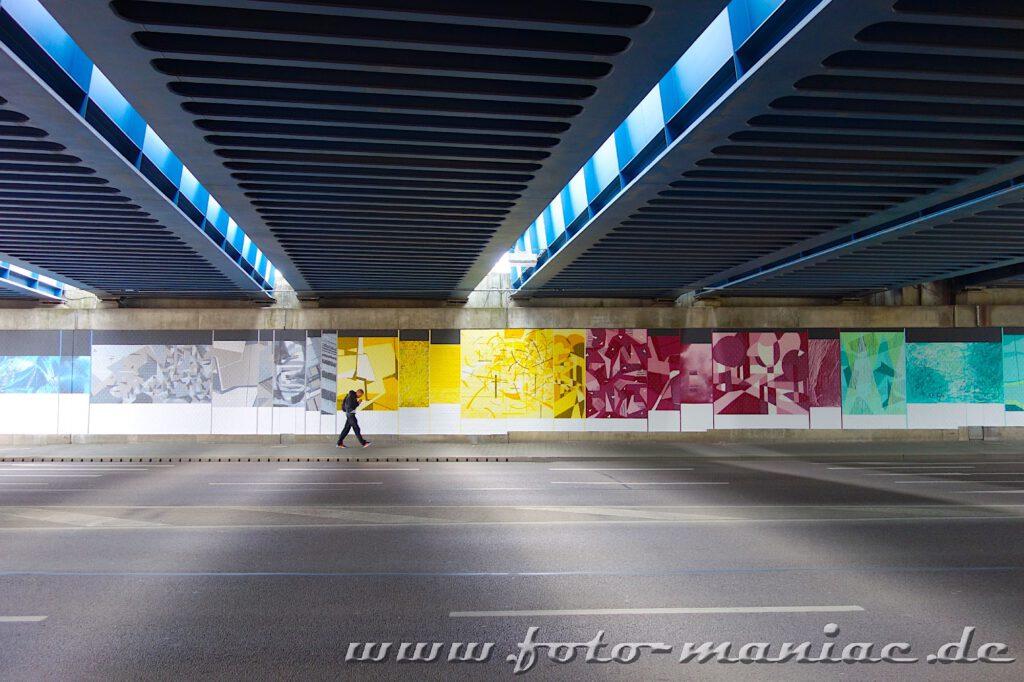 Ein Mann läuft vor einer Graffiti-Wand
