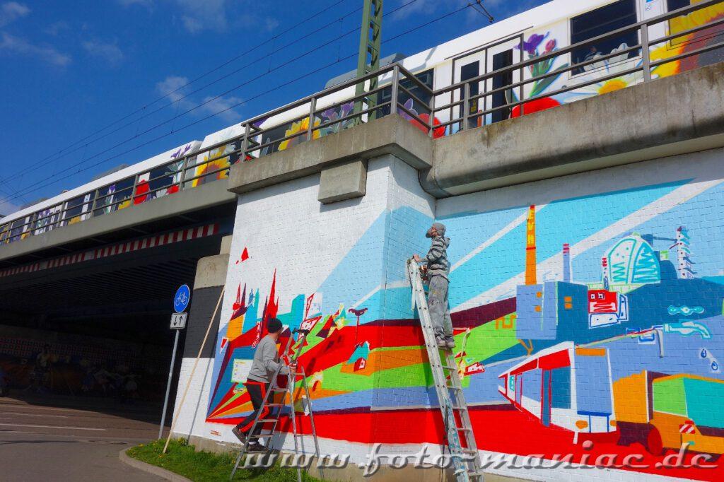 Zwei Streetart-Künstler bringen Graffito an Bahnbrücke an