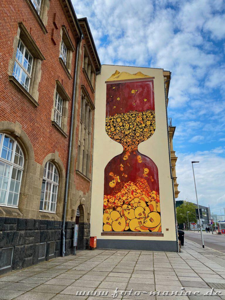 Schöne Graffiti in Halle - Köpfe als Körner in einer Sanduhr auf eine Fassade gemalt