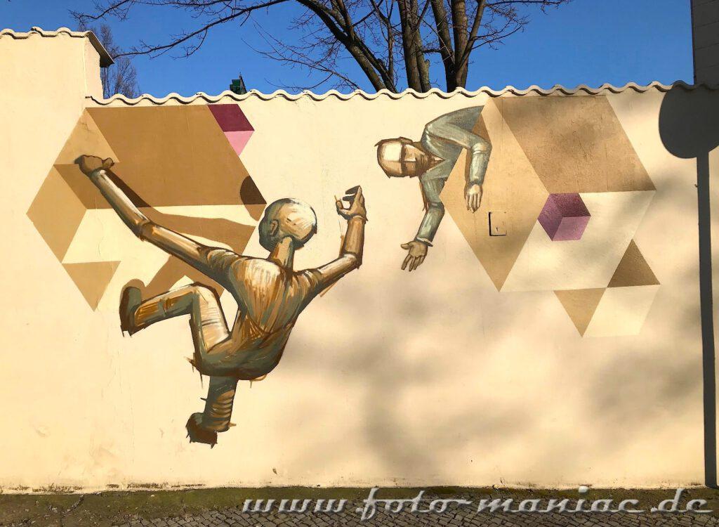Figuren mit Würfeln an einer Mauer