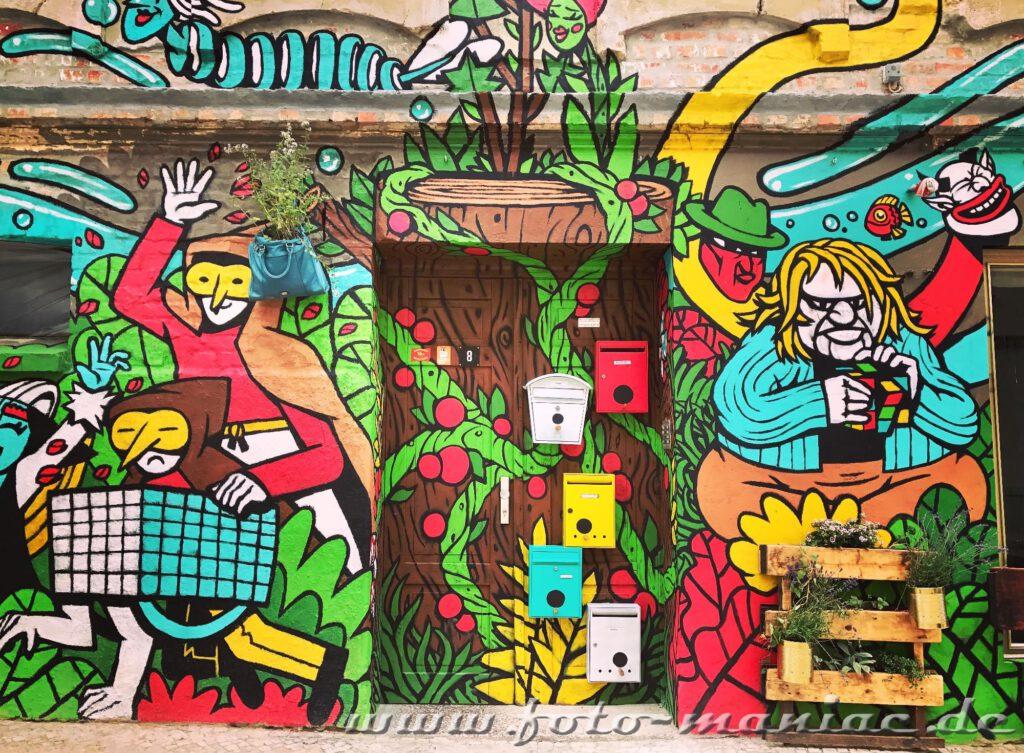 Bunte Briefkästen an der Tür und Figuren auf die Wand gemalt