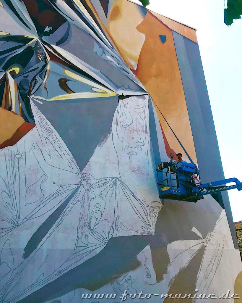 Graffiti-Künstler winkt von der Hebebühne