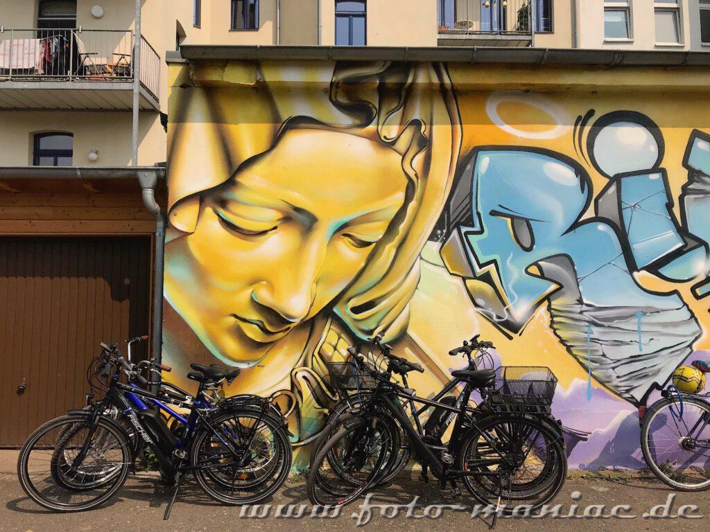 Fahrräder vor einem Madonnen-Graffito