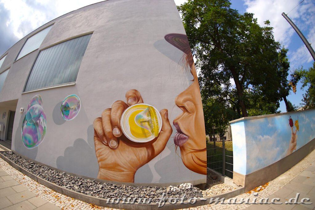 Mauer-Graffito: Kind bläst Seifenblasen in die Luft