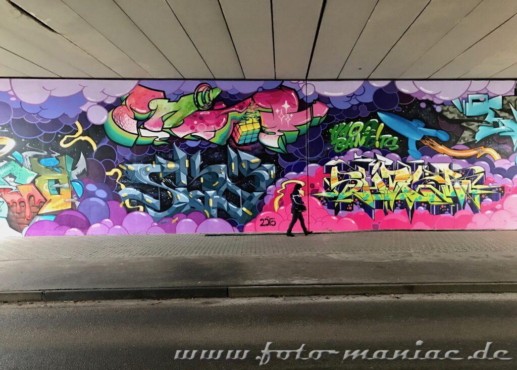 Frau läuft in einer Unterführung vor einem Graffito