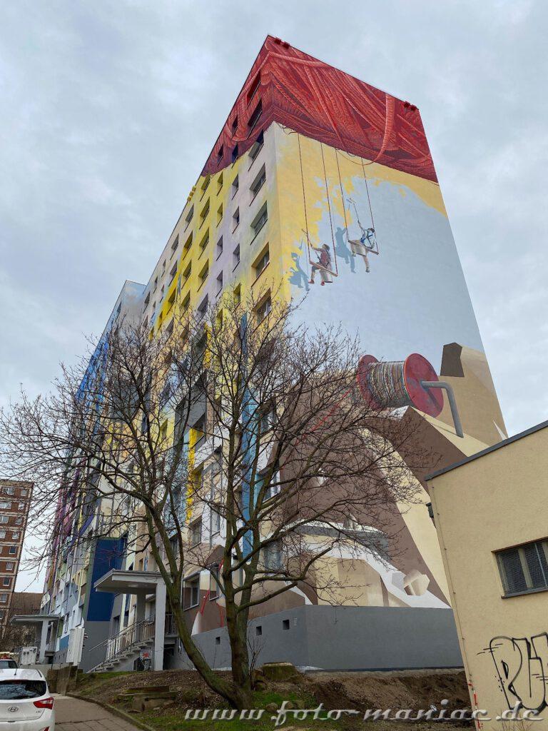 An einer Graffiti-Hauswand seilen sich Figuren ab