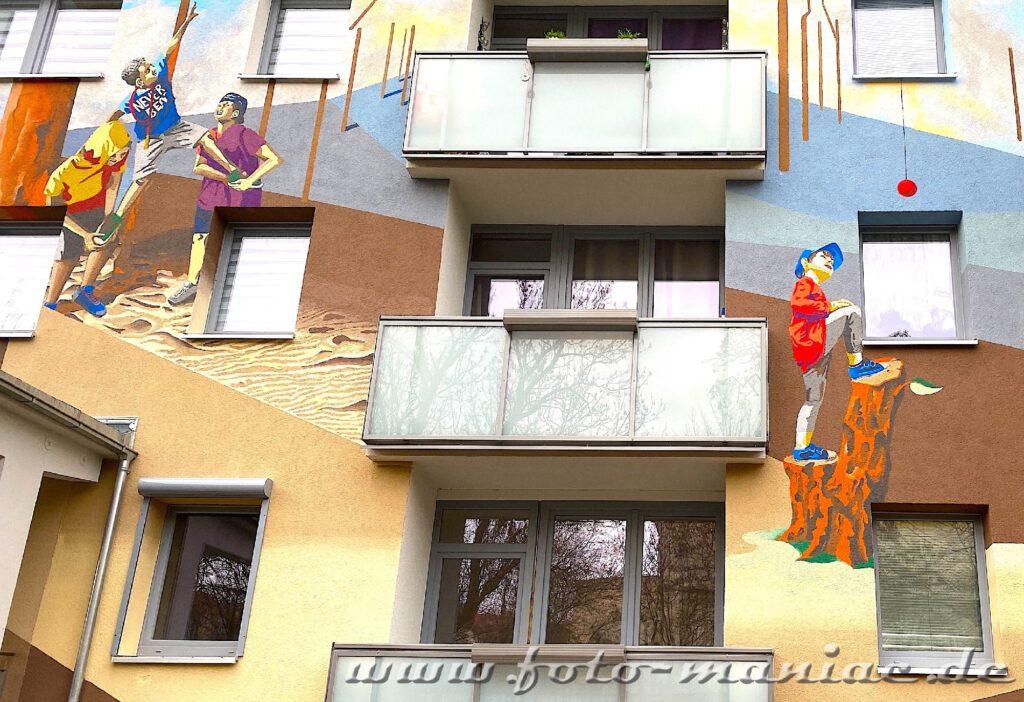 Vier Figuren an einer Graffiti-Hauswand