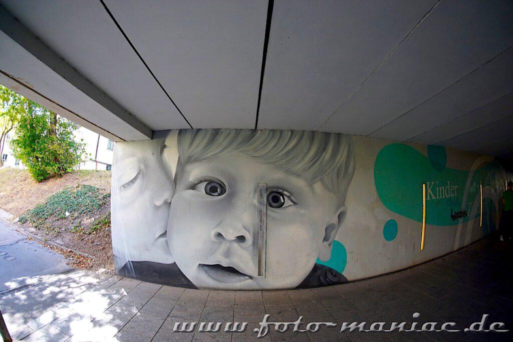 Kindergesicht-Graffito in einem Fußgängertunnel