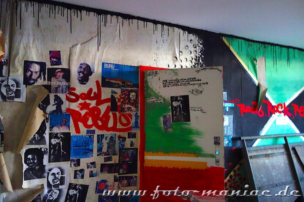 Wand ist mit Porträtfotos beklebt