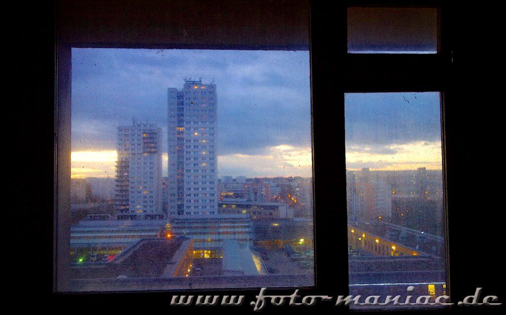 Marode Platte -Blick aus einem Fenster auf die Silhouette von Halle-Neustadt im Dämmerlicht