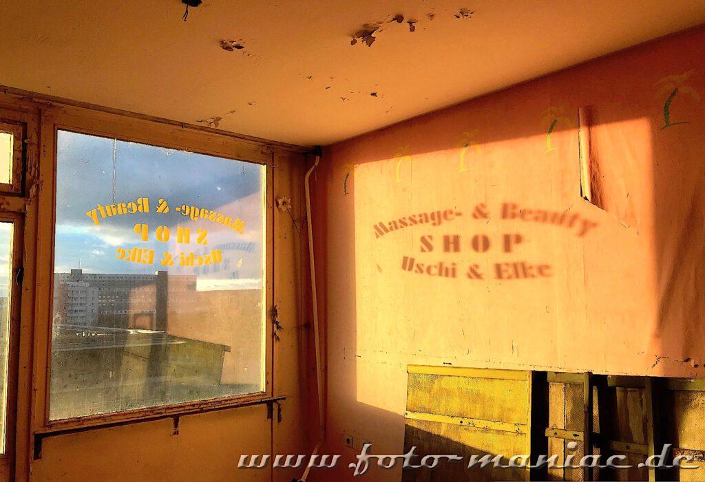 Marode Platte - Spiegelung eines Shop-Namens auf der Wand