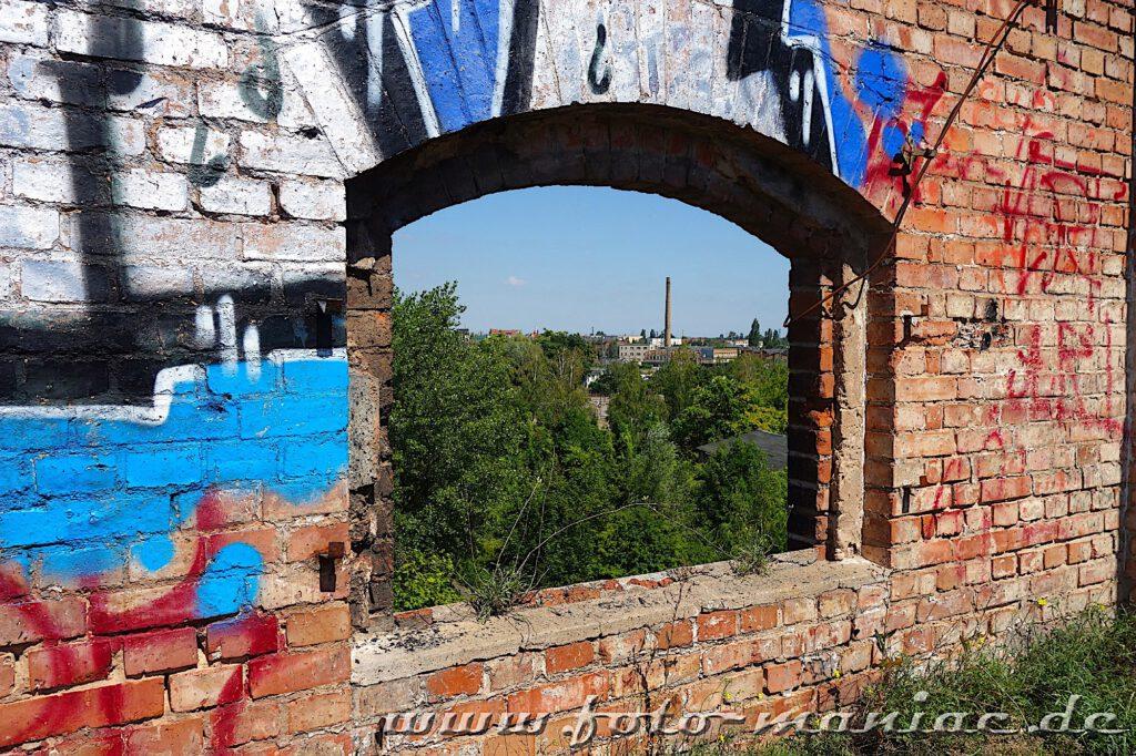 Durch einen Fensterdurchbruch geht der Blick von der verlassenen Spritfabrik in Halle zu einem Schornstein