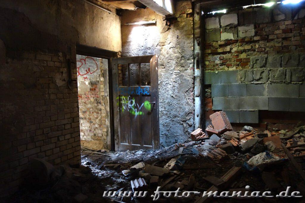 Hinter einen Trümmerhaufen steht eine Tür offen