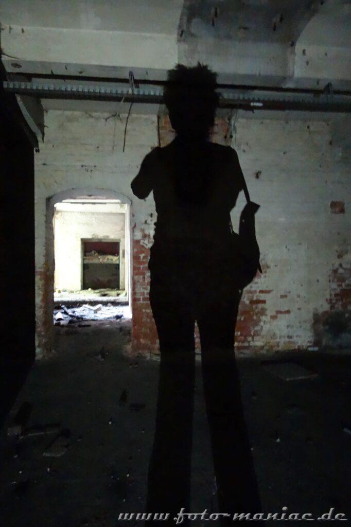 Schattenspiel in der verlassenen Spritfabrik in Halle einen menschlichen Schatten an die Wand