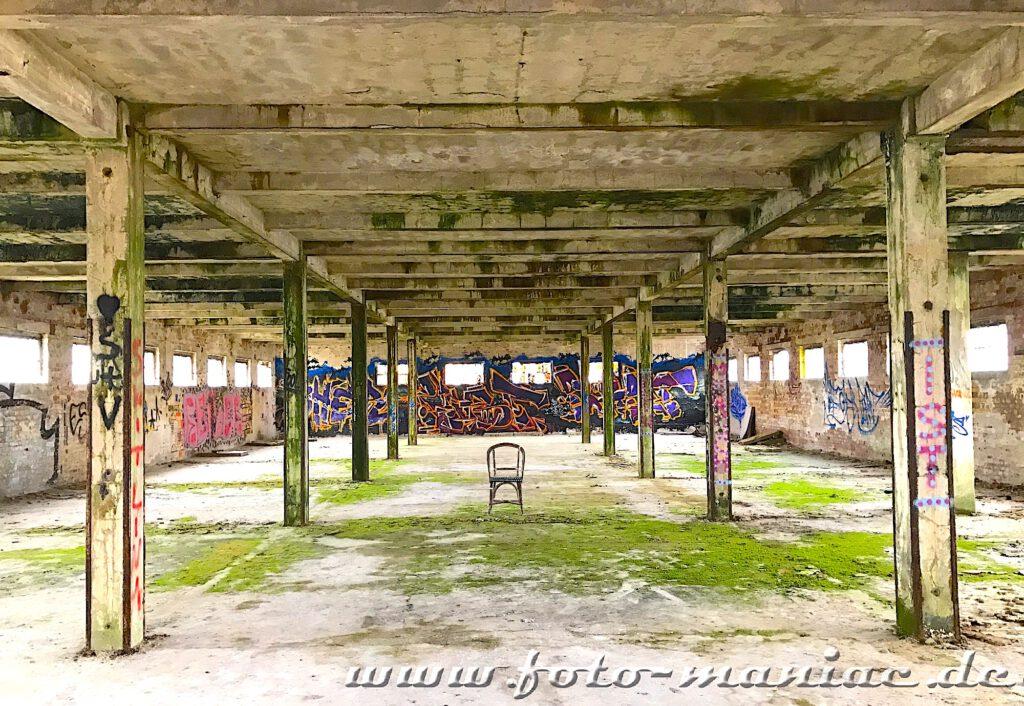 Ein Stuhl zwischen Pfeilern in leerer Halle in der verlassenen Brauerei Sternburg