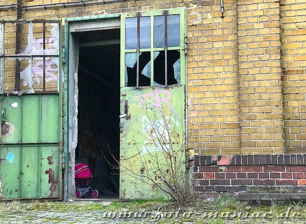 Hinter einer halb geöffneten Hallen-Tür steht ein roter Puppenwagen