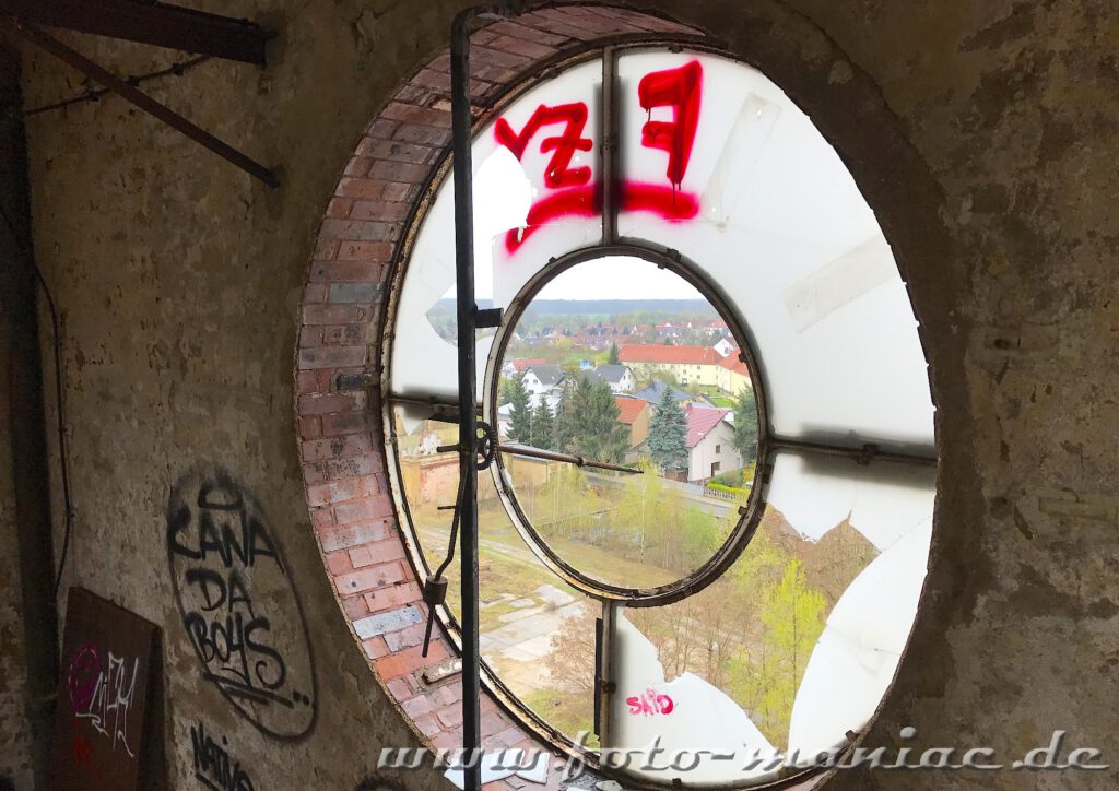 Durch die Reste einer Turmuhr der verlassenen Brauerei Sternburg geht der Blick auf Lützschena