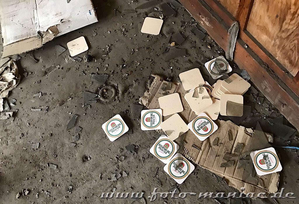 Bierdeckel von der Marke Sternburg liegen auf dem verschmutzten Boden