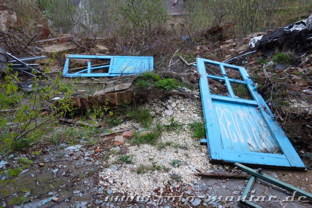 Zwei blaue zerstörte Türen liegen auf dem Boden