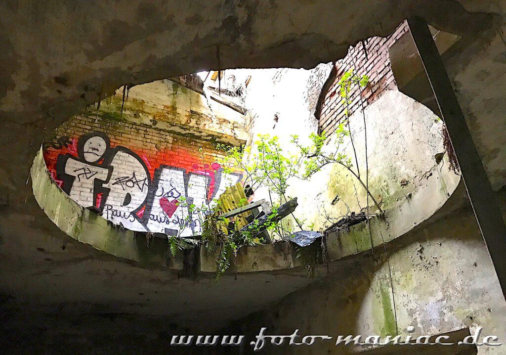 Ein Graffiti-Tag ist durch eine kreisrunde Öffnung zu sehen