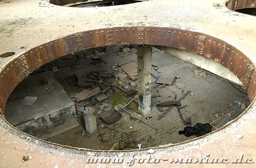 Blick durch die kreisrunde Öffnung geht der Blick ins untere Geschoss der verlassenen Brauerei Sternburg