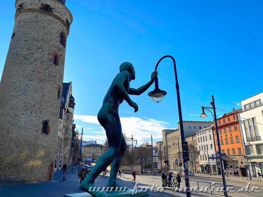 Nackte Skulptur greift nach Bogenlampe
