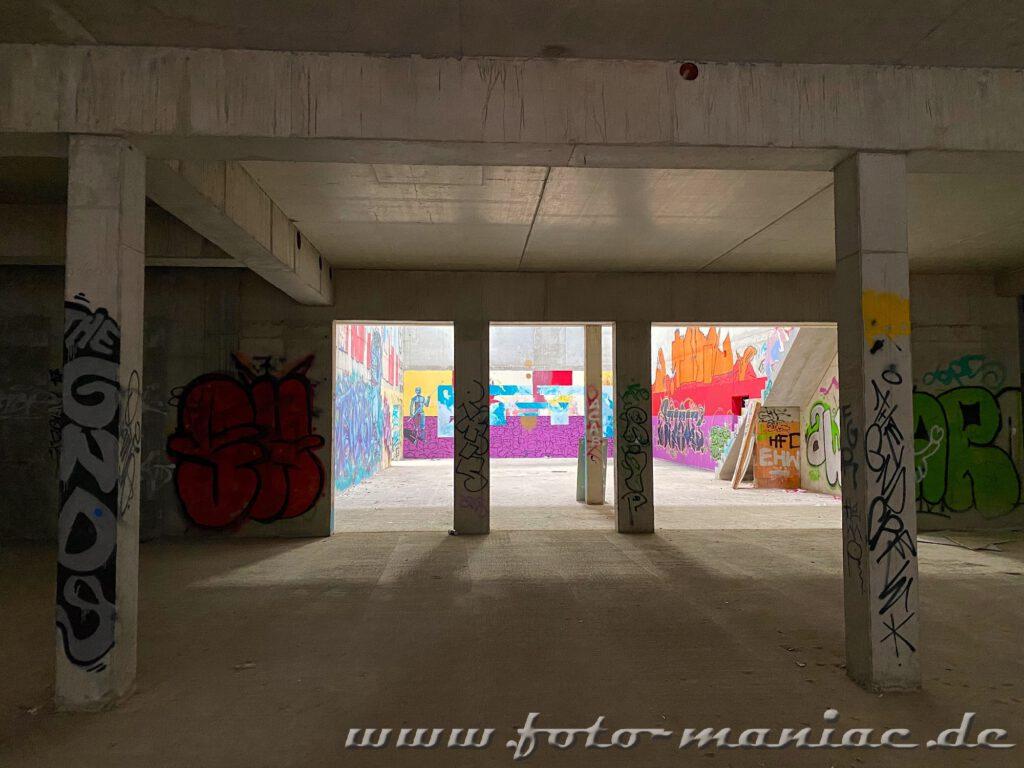 Hinter den Säulen leuchtet eine Wand mit Graffiti