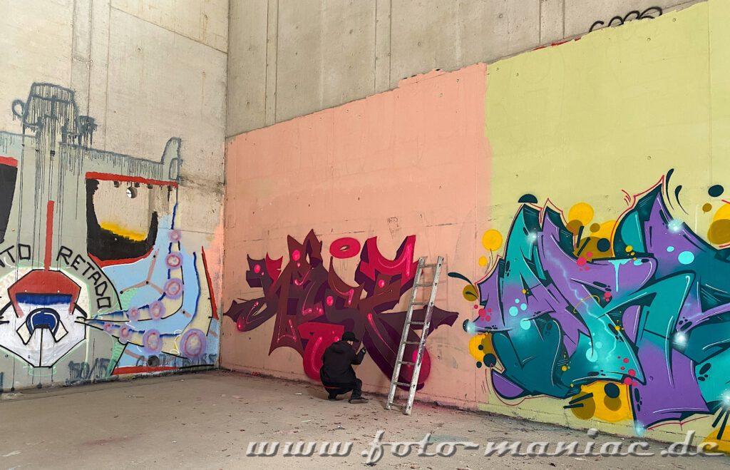 Graffiti-Künstler gestaltet eine Wand