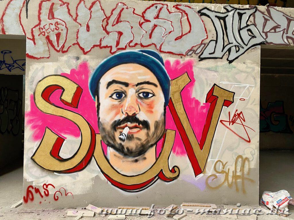 Mann mit Zigarette und Mütze - Graffiti im Sportkomplex