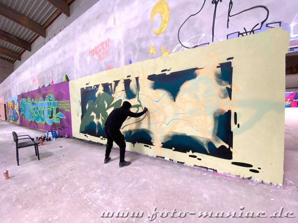 Graffiti-Künstler malt ein Bild an einer Wand