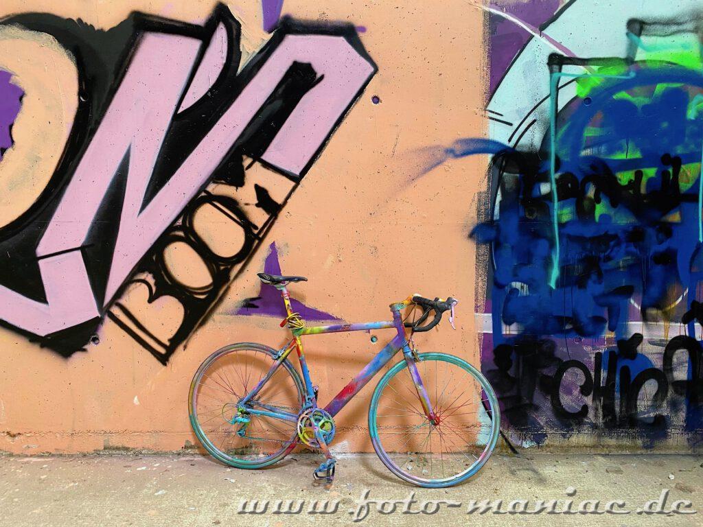 Mit bunten Farben besprühtes Rennrad vor Graffiti in Turnhalle