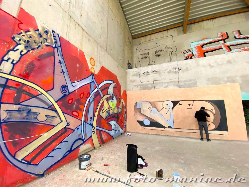 An einer Wand der Sporthalle wird ein Bild gemalt
