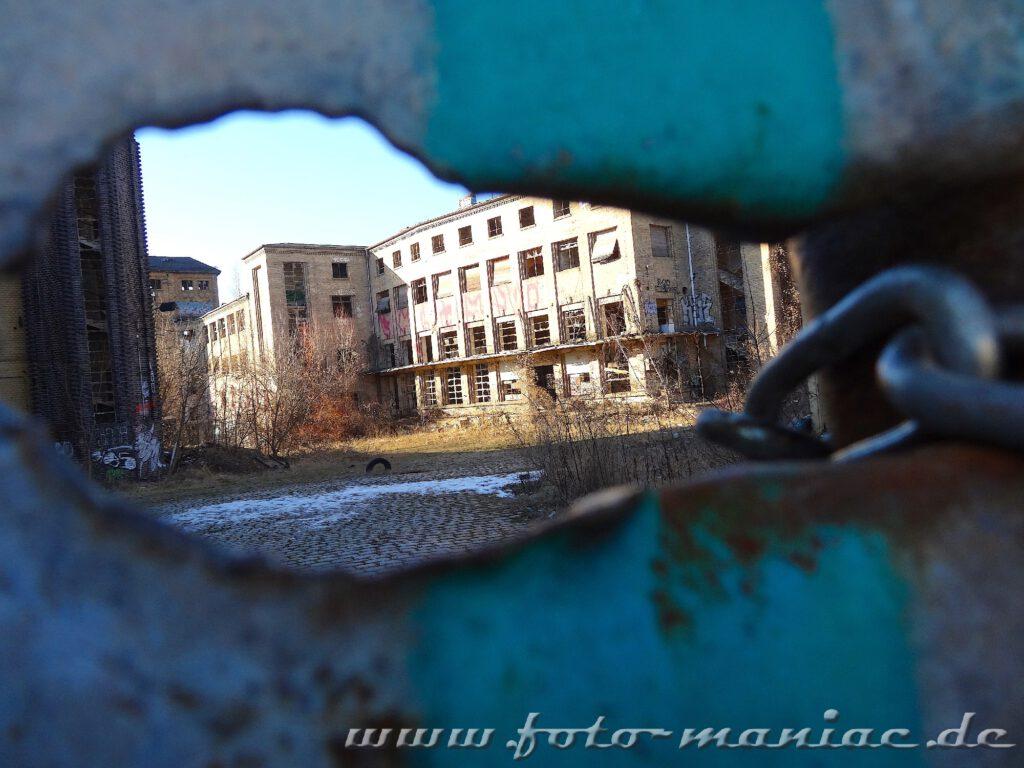 Blick durch ein Loch aufs Gelände der maroden Freyberg Brauerei in Halle