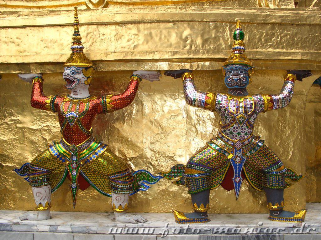 Thailands schmucke Juwelen - zwei üppig dekorierte Figuren an einem Palast-Gebäude