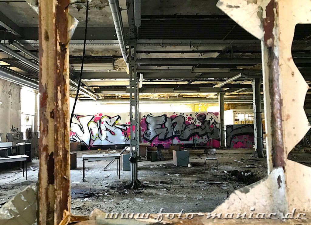 Blick durch die zerschlagenen Fensterscheiben in eine kleine Werkhalle