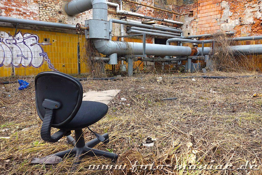 Ein Bürostuhl steht vor einem maroden Gebäude