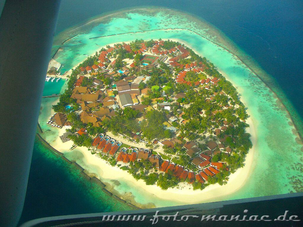 Traumurlaub auf den Malediven - Flugzeug fliegt über einer Ferieninsel