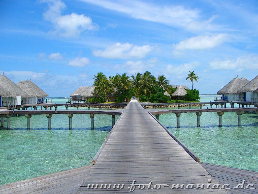 Traumurlaub auf den Malediven - Stege verbinden die im Wasser stehenden Bungalows